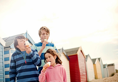Girl and two boys (5-10) licking ice creams at the beach, Southwold, Suffolk, United Kingdom - p300m2298744 von LOUIS CHRISTIAN