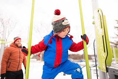 Boy with father climbing up playground slide in snow - p924m2074511 by Viara Mileva