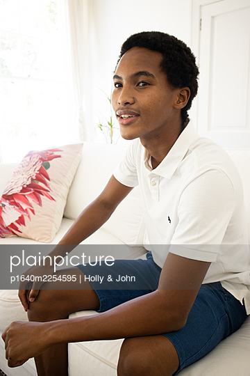 Dark-skinned boy on the sofa - p1640m2254595 by Holly & John