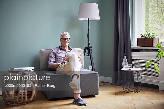 Portrait of smiling mature man using tablet at home - p300m2030193 by Rainer Berg