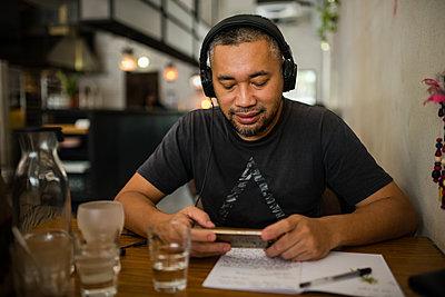 Asian man listening music on headphones - p1166m2131265 by Cavan Images