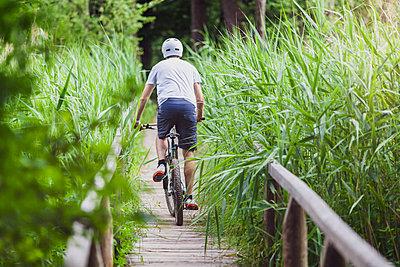 Man on mountain bike crossing a bridge at a lake - p300m2083853 von Michael Malorny