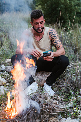 Man sitting at campfire in rural landscape using cell phone - p300m2114624 by DREAMSTOCK1982