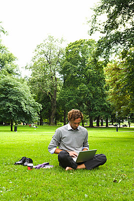 A man with a laptop in a park Sweden. - p31221342f by Plattform