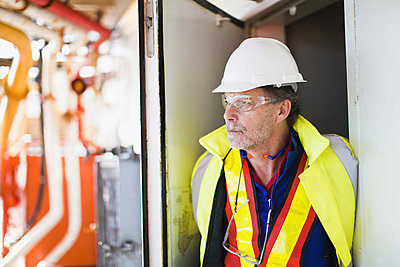 Worker standing in doorway on oil rig - p42915029f by Hybrid Images