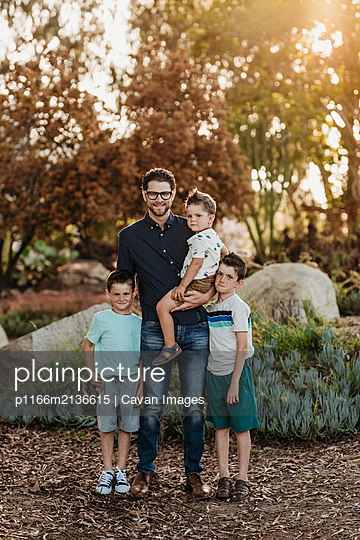 Full length portrait of father and young sons making goofy faces - p1166m2136615 by Cavan Images