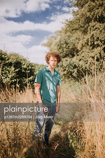 Young man in tall grass, portrait - p1267m2259704 by Jörg Meier