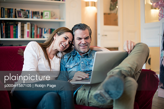 Happy couple sitting on couch using laptop - p300m1587105 von Robijn Page