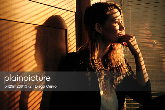 Young woman by window at sunset - p429m2091372 by Diego Cervo