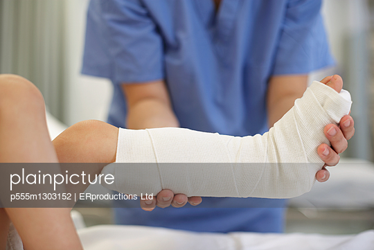 Medical professional holding child\'s leg in cast