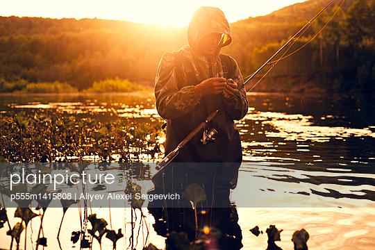 Mari fisherman preparing hook in lake  - p555m1415808 by Aliyev Alexei Sergeevich