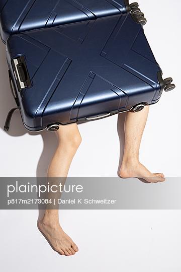 Naked man hiding behind trolleybag - p817m2179084 by Daniel K Schweitzer