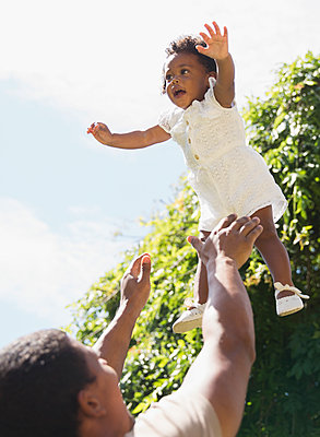 Father throwing daughter overhead playfully in sunshine - p1023m2212780 by Tom Merton