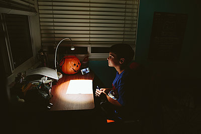 Boy sits in the dark at his desk while on a video call with a friend - p1166m2201200 by Cavan Images