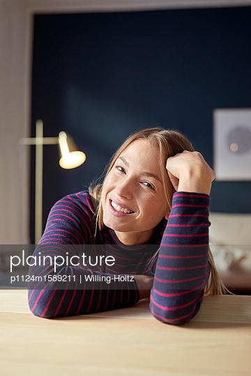 Junge Frau entspannt sich in ihrer Wohnung - p1124m1589211 von Willing-Holtz