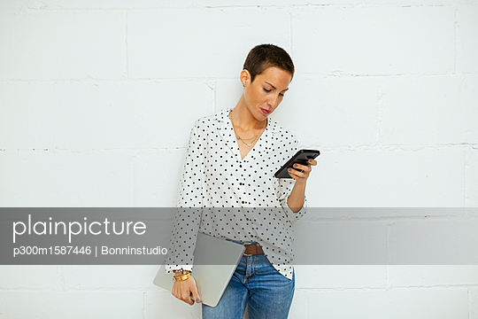 Young woman standing at brick wall looking on cell phone - p300m1587446 von Bonninstudio