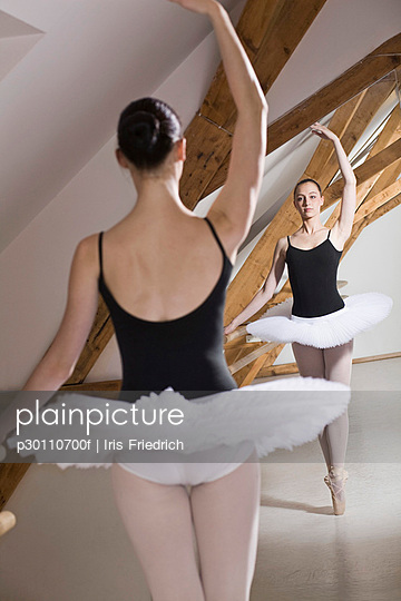 A ballet dancer on pointe with one arm raised in front of a mirror in a ballet studio