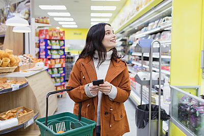 Woman with smart phone shopping in supermarket - p1023m2187652 by Sam Edwards