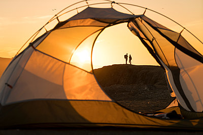Distant view of couple standing on rock formation seen through tent during sunset - p1166m1194048 by Cavan Images