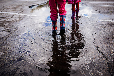 Low section of siblings walking on puddle - p1166m1474041 by Cavan Images