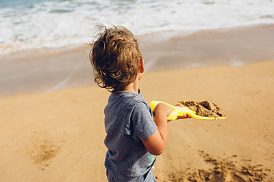 Side view of boy playing with shovel and sand at beach - p1166m1543255 by Cavan Social