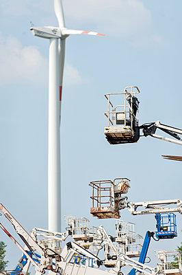 Alte Hebebühnen und moderne Windkraftanlage im Hintergrund - p229m1574857 von Martin Langer