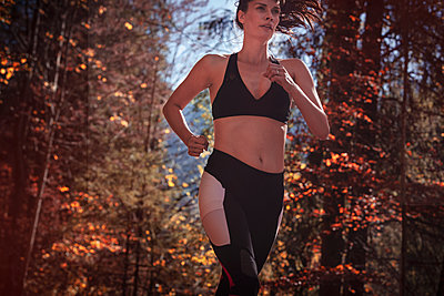 Woman jogging in autumn forest - p300m2166369 by Studio 27