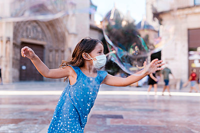 Carefree girl wearing mask running on street in city playing with soap bubble - p300m2220682 by Ezequiel Giménez