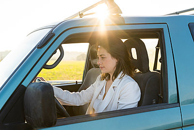 Beautiful woman on road trip driving car during sunset - p300m2239903 by VITTA GALLERY