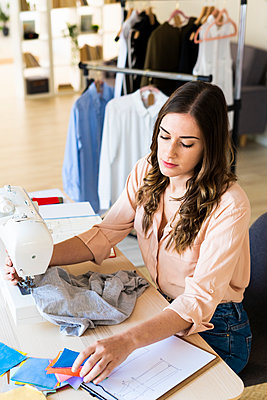 Young female fashion designer looking at fabric swatches while sewing on machine in studio - p300m2240565 by Giorgio Fochesato