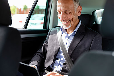 Smiling businessman using laptop in car - p300m2287341 by Emma Innocenti