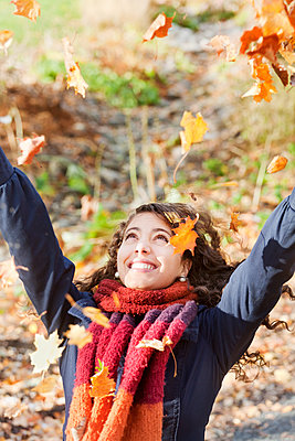 Young cheerful woman scattering autumn leaves on sunny day - p312m1551981 by Johner Images