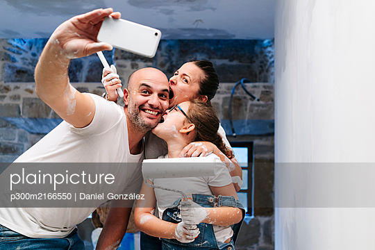 Happy family taking a selfie while painting the walls of her new house - p300m2166550 von Daniel González