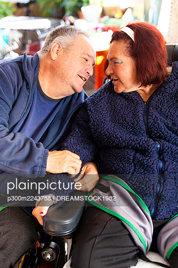 Disabled heterosexual couple sitting at rehabilitation center - p300m2243788 by DREAMSTOCK1982