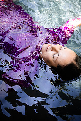 Woman in purple dress swims backstroke - p1640m2245825 by Holly & John