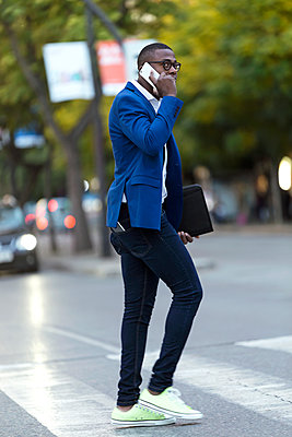 Young businessman wearing blue suit jacket crossing the road and using smartphone - p300m2114592 von Josep Suria