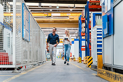 Businesswoman and male colleague discussing while walking in factory - p300m2240096 by Daniel Ingold