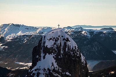 Cross on snowy mountaintop - p924m768379f by Julian Ward