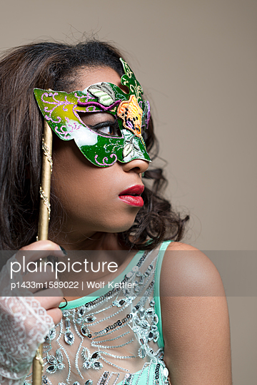 Glamorous young black woman wearing a Venetian mask. - p1433m1589022 by Wolf Kettler