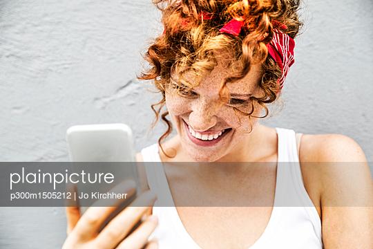plainpicture | Photo library for authentic images - plainpicture p300m1505212 - Happy redheaded woman holdi... - plainpicture/Westend61/Jo Kirchherr