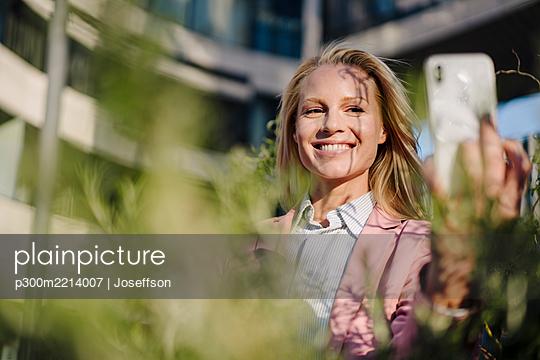 Smiling beautiful female entrepreneur taking selfie on sunny day - p300m2214007 by Joseffson