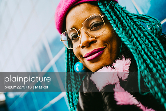 Portrait of smiling braided hair woman wearing eyeglasses and pink lipstick - p426m2279713 by Maskot