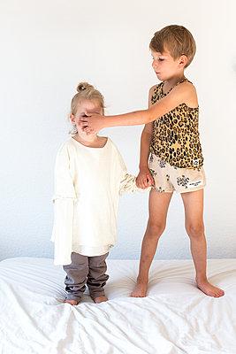 Großer Bruder hält seine Hand vor das Gesicht seiner kleinen Schwester - p1301m1465625 von Delia Baum