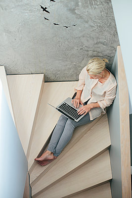 Woman with laptop sitting on stairs - p312m1180357 by Anna Rostrom