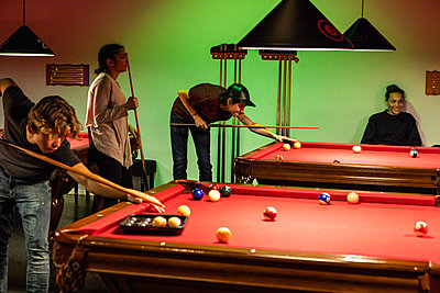 Teenagers playing pool on illuminated red tables - p426m1588384 by Maskot