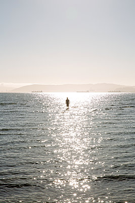Person wading through shallow water, Pacific Ocean, USA - p756m2211774 by Bénédicte Lassalle