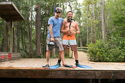 Friends wearing snorkels and swimming flippers on jetty, Niceville, Florida, USA - p924m1422737 by Raphye Alexius