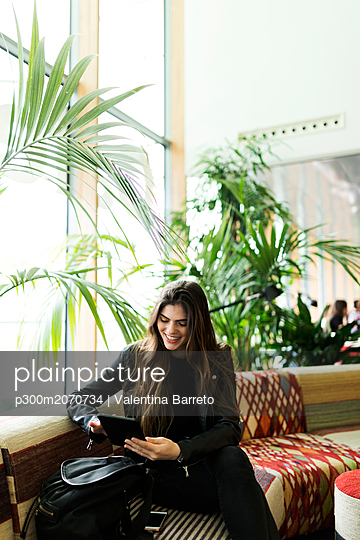 Smiling young woman sitting in a lounge using tablet - p300m2070734 by Valentina Barreto