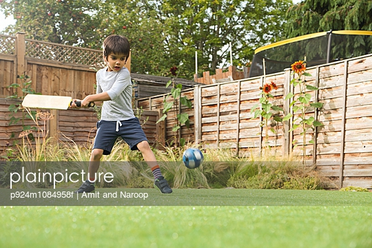 Boy playing cricket in garden, ball in mid air