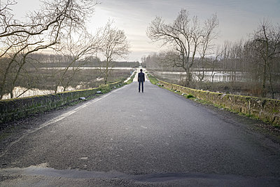 Man standing on rural road - p1402m2148313 by Jerome Paressant
